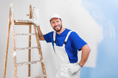 Photo for Portrait of handsome young smiling painter in white dungarees, blue t-shirt, cap and gloves leaning on a vintage ladder with paint roller, looking at camera - Royalty Free Image