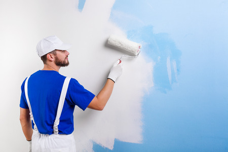 Foto de Back view of handsome young painter in white dungarees, blue t-shirt, cap and gloves painting a wall with paint roller. - Imagen libre de derechos