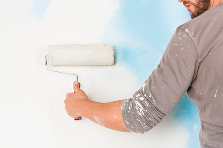 Photo for Close up of painter arm in splattered paint shirt painting a wall with paint roller; copy space - Royalty Free Image