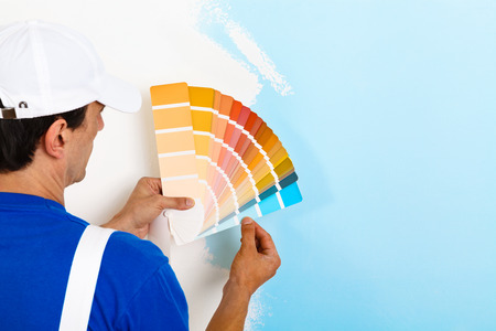 Photo for rear view of painter man looking a color palette on half painted wall, with copy space - Royalty Free Image