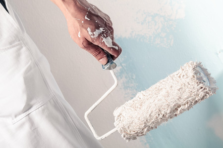 Foto de Close up Of Professional Workman Hand holding Dirty Paintroller - Imagen libre de derechos