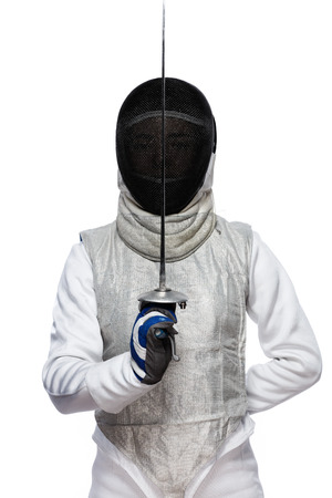Foto de Portrait of Young woman fencer wearing mask and white fencing costume and holding the sword in front of her. Isolated on White Background - Imagen libre de derechos