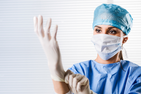 Foto de Portrait of Female doctor Surgeon in blue scrubs putting on surgical gloves - Imagen libre de derechos