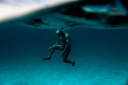 Photo for interesting under-water view of a Senior man floating on the ocean. - Royalty Free Image