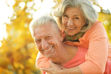 Foto de Beautiful happy old people in the autumn park - Imagen libre de derechos