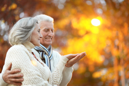 Photo pour Beautiful happy old people in the autumn park - image libre de droit