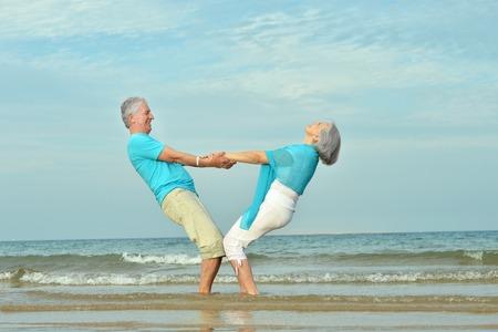 Photo pour Beautiful happy elderly couple walking along the seashore - image libre de droit