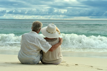 Foto de Beautiful happy elderly couple rest at tropical resort - Imagen libre de derechos
