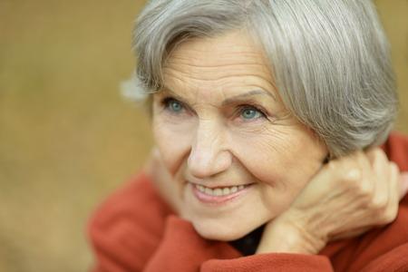 Photo for Happy elderly woman enjoying in autumn park - Royalty Free Image