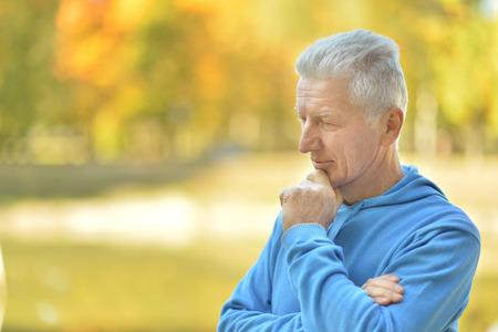 Foto de Portrait of senior man thinking about something outdoor - Imagen libre de derechos