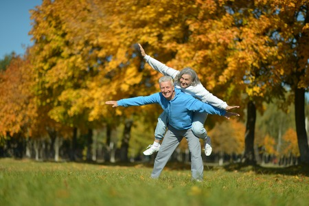 Portrait of a happy senior couple resting at autumn park
