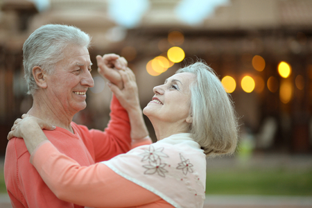 Senior couple resting at the resort during vacation on dance floor