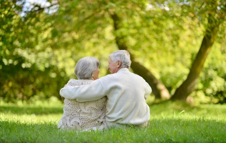 Foto de Happy elderly couple sitting in autumn park - Imagen libre de derechos
