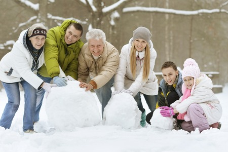 Photo pour happy young family playing in fresh snow and building snowman at beautiful sunny winter day outdoor in nature - image libre de droit