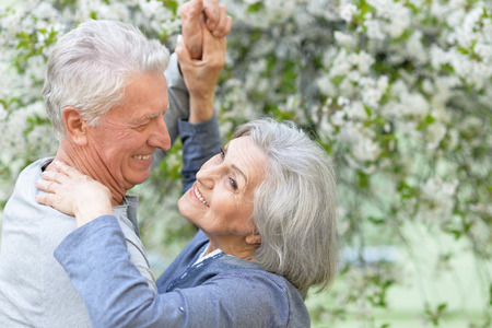 Foto per Nice Mature couple dancing in spring park - Immagine Royalty Free