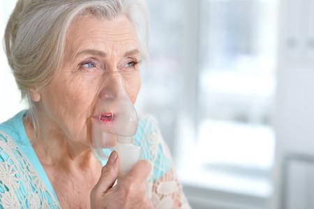 Photo pour Sick elderly woman making inhalation - image libre de droit