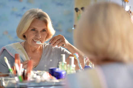 Photo pour Senior woman brushing her teeth - image libre de droit