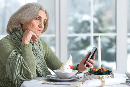 Foto de woman sitting at table  with phone - Imagen libre de derechos