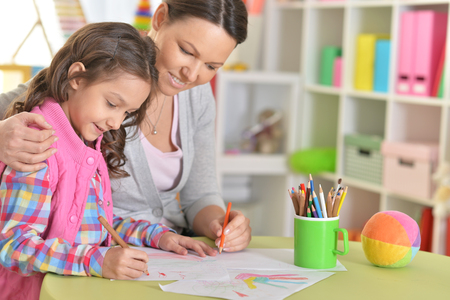 Photo pour Mother and daughter sitting at table and drawing - image libre de droit