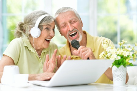 Foto de happy senior couple singing karaoke with laptop - Imagen libre de derechos