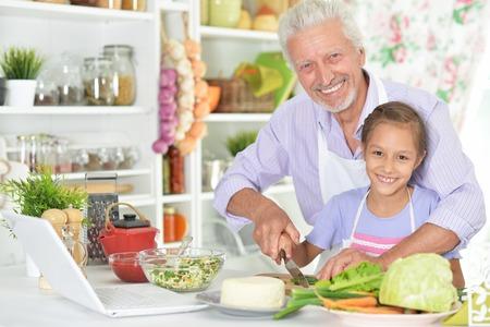 Foto de Senior man with granddaughter preparing dinner in kitchen - Imagen libre de derechos