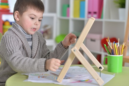 Foto de Portrait of little boy sitting at table and learning to use abacus - Imagen libre de derechos