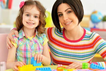 Foto de Close up portrait of cute little girl and her mother playing colorful plastic blocks together in her room - Imagen libre de derechos