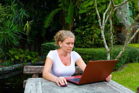 Foto de A woman is working on the computer. In the open air. - Imagen libre de derechos