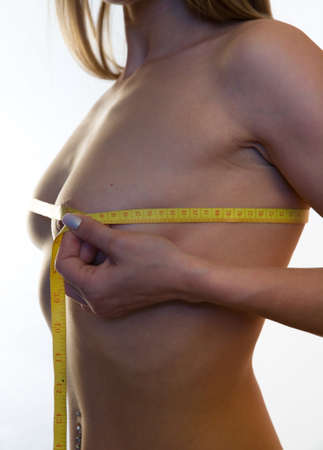 Photo pour A beautiful naked girl measures the volume of her breast. Part of the body. - image libre de droit