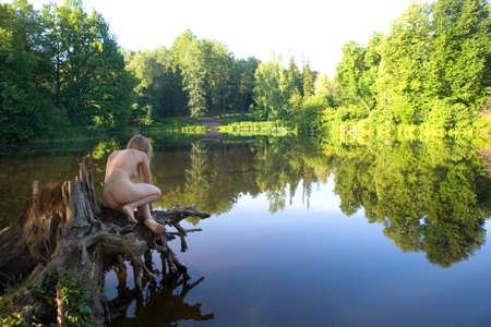 Photo for A beautiful naked girl sits on a picturesque stump. Morning in nature. - Royalty Free Image
