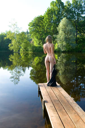 Photo for A slender naked girl stands on the bridge against the backdrop of a picturesque pond. Erotica and nature. - Royalty Free Image
