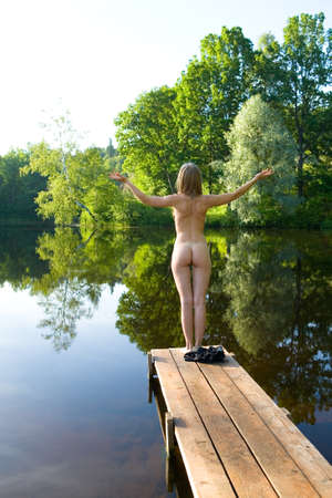 Photo pour The naked girl stands on the bridge against the backdrop of a picturesque pond. Hands are raised in the sides. Erotica and nature. - image libre de droit