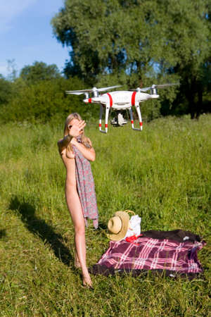 Foto per The girl covers her nakedness with her dress. The drone looks at her. Interference in private life. Attention! Focus on the drone! - Immagine Royalty Free