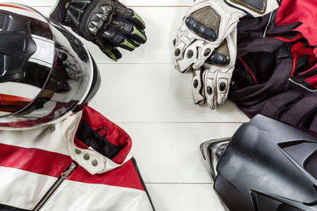 Photo pour Overhead view of biker accessories placed on white wooden table. - image libre de droit