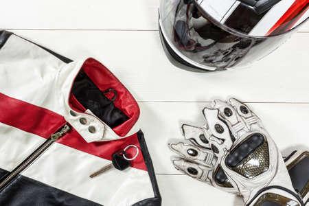 Foto de Overhead view of biker accessories placed on white wooden table. Items included motorcycle helmet, gloves, keys and jacket. Motorcycle travel dream concept. - Imagen libre de derechos