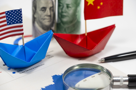 Photo pour US dollar of United of America and Yuan China banknotes with flag on ship with import export financial report for analysis economy after both countries announce tax tariff trade war. - image libre de droit