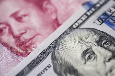 Foto de Close up of of China Yuan banknote and US dollar for trade war and economic tax barrier concept. - Imagen libre de derechos