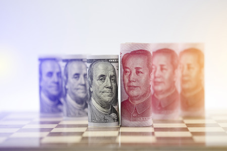 Foto de US dollar and Yuan banknote on chessboard for trade war between United States and China which both countries battle by increase tax barrier of import and export product. Government and business. - Imagen libre de derechos