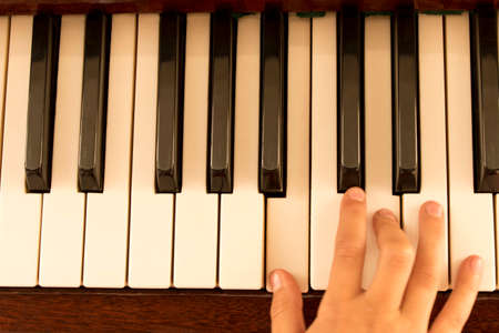 Foto de The girl's hand on the piano keys. Piano keys background. Selective focus. - Imagen libre de derechos