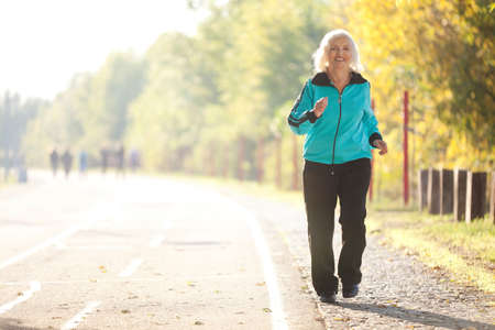 Foto per 70 years old Senior Woman Jogging at the Pedestrian Walkway in the Bright Autumn Evening - Immagine Royalty Free