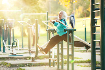 Photo pour Woman doing Exercises for Legs Outdoors in the Bright Autumn Evening - image libre de droit
