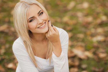 Close up portrait of young blonde beautiful woman in warm autumn scarf  Ourdoors