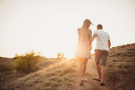 Foto de Young couple in love, an attractive man and woman enjoying a romantic evening, holding hands to watch the sunset - Imagen libre de derechos
