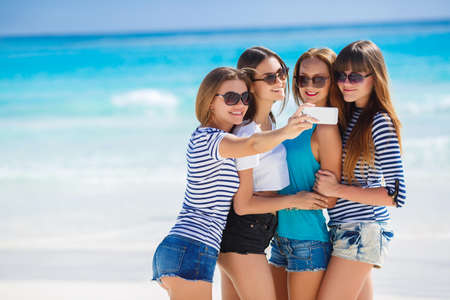 Photo for Beautiful girls are photographed on a tropical resort on the background of the beach and ocean.Four young beautiful girls - brunette, long straight hair, in shorts and T-shirts, sun glasses, with a beautiful smile, photographed on a smartphone on the back - Royalty Free Image
