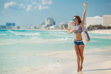 Photo for A beautiful young woman,a brunette with long straight hair,in blue shorts, wearing sun glasses with blue glasses, striped beach bag and a striped t-shirt,standing near the ocean enjoying the vacation on a tropical resort. - Royalty Free Image