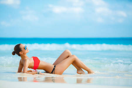 Attractive and sexy girl on the beach. Young female enjoying sunny day on tropical beach. Beautiful girl sunbathing under summer sun lying in sand on beach with blue water