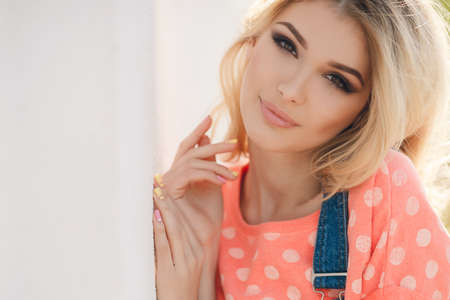 Summer portrait of a beautiful woman. Very beautiful blonde girl with big brown eyes bushy long hair dressed in a pink Tshirt with white polka dots and denim overalls in dark blue green park resting in a sunny summer day