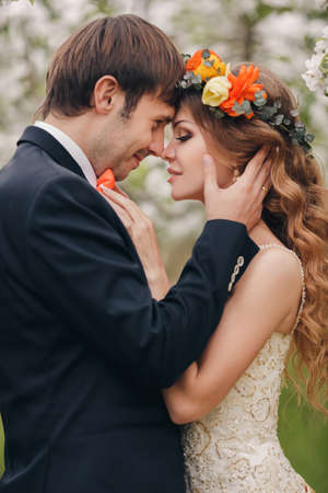 Foto de Wedding couplethe groom is a young darkhaired man in a black suit and pink bow tiebeautiful bridebrunette with long curly hair in a white wedding dress on her head a wreathposing embracing in the Park among the blooming trees. - Imagen libre de derechos