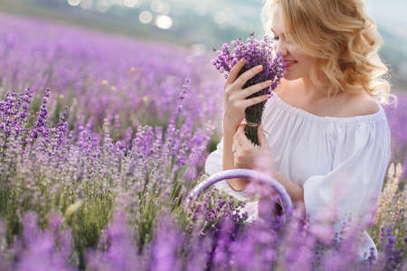 Photo for Beautiful Bride in lavender field. Newlywed woman in lavender flowers.Young woman in wedding dress outdoors. Beautiful young woman in white dress posing in a lavender field with small wicker basket - Royalty Free Image
