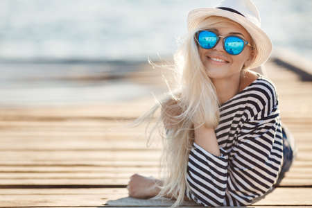 Photo pour Beautiful young woman with long blonde straight hair, sunglasses with blue glasses, shorts and a striped shirt sailor, spends time resting on a wooden pier near the sea - image libre de droit